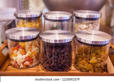 sweet colorful glass mugs, jars or bottles on display in wooden tray in kitchen or pantry for toppings (jelly, currants, sultanas, raisins, grapes, cereal) or ingredients of dessert, snack, ice cream.