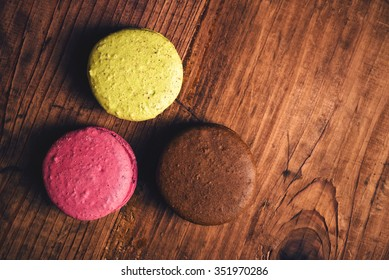 Sweet colorful homemade macaron cookies on table, retro toned, top view
