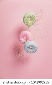 Sweet and colourful doughnuts with sprinkles falling or flying in motion against pastel pink background