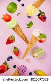Sweet and colourful ice cream in waffle cones with sprinkles  and ingredients falling or flying in motion against pink shabby chic vintage background