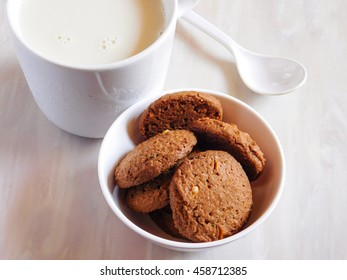 sweet cookies in white bowl with milk in glass
