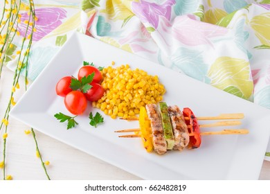 Sweet corn. Vegetables and chicken meat grilled on skewers. Cherry tomatoes. Children's menu in the restaurant. A healthy, nutritious, balanced diet for children.