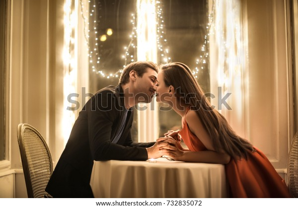Sweet couple kissing in a romantic dinner