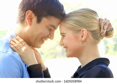 Sweet couple showing love by touching heads in park, young beautiful woman puts her arms around her boyfriend's neck, lover hugging each other, spending time together and having romantic moment