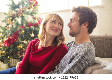 Sweet couple sitting in the living room, celebrating christmas - Shutterstock ID 1222479628