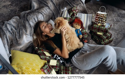 Sweet couple of young girl and her maltipoo doggy. Lying on grey couch with pillows and christmas gifts. Family and friends, love and friendship. Red curly hair, curved small tail. Smile and laughing.