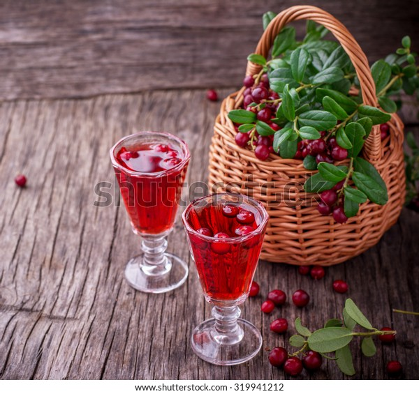 Sweet cranberry liqueur in two glasses on the background of ripe berries on a dark wooden background. selective Focus