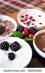 Sweet cream dessert with chocolate and berries in white porcelain bowls on wooden plate with ceramics measuring spoons. Checkered tablecloth.