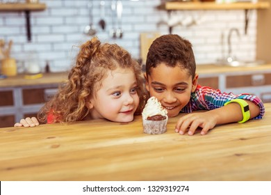 Sweet cream. Funny girl staring at cake while leaning chin on table