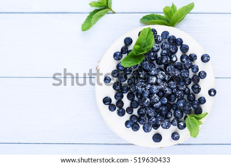Sweet creamy blueberry cheesecake with fresh blueberries and mint leaves on a white wooden background with copy space.