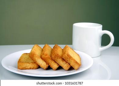 Sweet crispy toast or rusk with coffee mug
