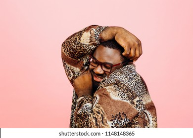 Sweet, cuddly man hugging himself, isolated on pink studio background