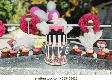 Sweet cupcakes and balls on sticks stand before birthday cake