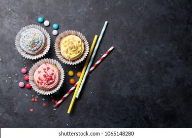 Sweet cupcakes with colorful decor and candies. Top view with space for your greetings