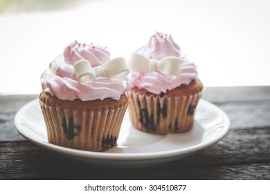 Sweet cupcakes on a wooden vintage background