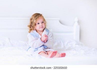 Sweet curly little girl in a white and blue bathrobe with a towel over her wet hair siting in a white sunny bedroom after shower or bath