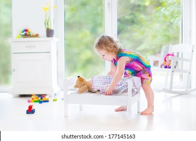 Sweet curly toddler girl playing with her teddy bear putting him in a toy bed to sleep in a sunny room with big garden view windows and white furniture
