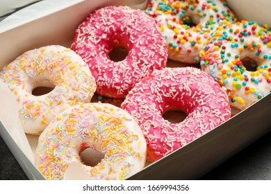 Sweet delicious glazed donuts on table, closeup