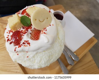 Sweet dessert Bingsu (Kakigori) topping with cheese cake, strawberry and smiley face cookie