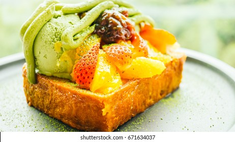 Sweet dessert bread toast with matcha ice cream and strawberry , orange in plate - Color filter Processing