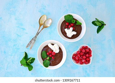 Sweet dessert, chocolate pudding in white portioned saucers on a light blue background. Decorated with mint and red currant berries. Valentine's Day concept. Top view.