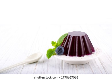 Sweet dessert jelly pudding with berries on white plate