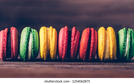 Sweet dessert macaroons of different colors in a row on wooden background, close-up.