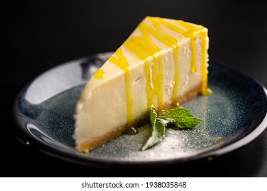Sweet dessert on a plate on a black background. Classic cheesecake with yellow lemon syrup. Copy space.