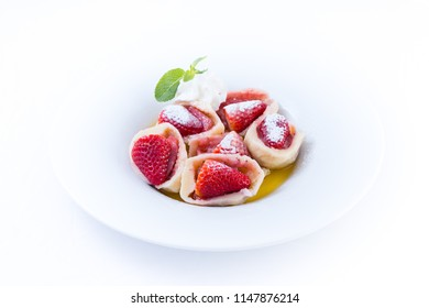 Sweet dessert served as an appetizer stuffed with dumplings with strawberries with whipped cream and sprig Pepermint on a white plate