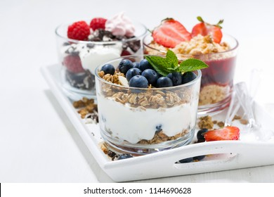 sweet desserts with fresh berries in glasses on white wooden tray, horizontal