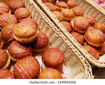 Sweet donuts, glazed and iced pastries in basket in bakery shop