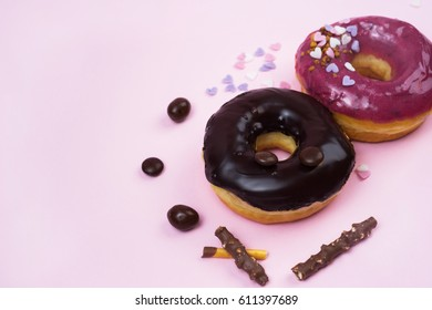 Sweet donuts with jam and chocolate topping on pink background, Selective focus.