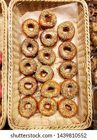 Sweet donuts with sprinkles, glazed and iced pastries in basket in bakery shop, top view