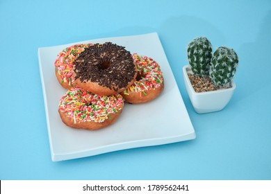Sweet doughnut cake stacks, there are cactus tree accessories set in a light blue background