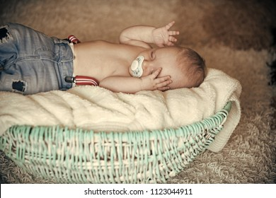 Sweet dream concept. Newborn boy with pacifier asleep in crib. Child in jeans sleep in basket on floor. Childhood, infancy, innocence. Nap, relax, tranquility.