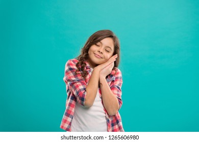 Sweet dream. Kid little girl hold hands at cheek as gesture of sleep. Good night and have nice dream. Sleepy peaceful baby on blue background. Wish sweet dreams. Lullaby song for small baby.