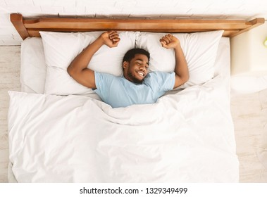 Sweet dreams. Peaceful black guy enjoying nap, resting in bed, top view with empty space