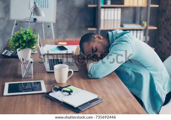 Sweet dreams in the work station. Sleepy tired freelancer is snoozing at his work place, coffee cup and office stuff near on desk top