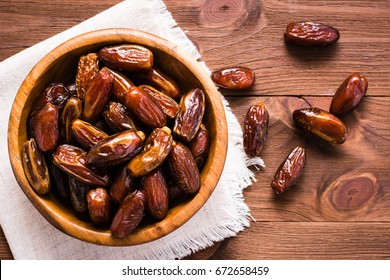 Sweet dried dates fruit in a wooden bowl and on the table. Top view