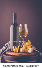 Sweet or dry white wine. Romantic composition from a wine bottle, glass of wine, an appetizer of hard cheese, brie cheese, figs, physalis. Postcard greetings.