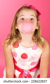 Sweet eight year old girl on a pink background blowing a big bubble with bubble gum