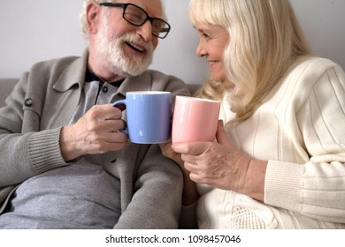 Sweet elderly couple having coffee at their house. Old man with glasses and beard drinking coffee with his wife on couch.