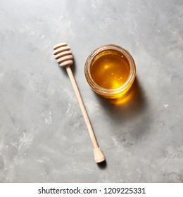 Sweet flower natural honey in a jar and wooden spoon on a gray concrete table, copy space. Top view. Jewish rosh hashanah holiday concept. Traditional useful sweetness.