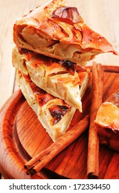 sweet food : apple pie cuts served on wooden plate over table with cinnamon sticks