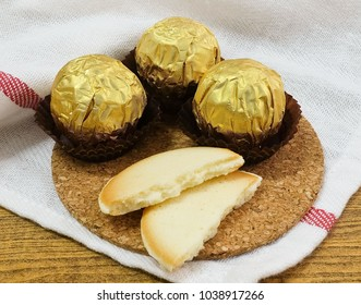 Sweet Food, Chocolate Candy Balls or Chocolate Bonbons in Golden Wrapper and Cookies, Crackers or Biscuits with Cream Cheese Filling on Round Cork Tray.