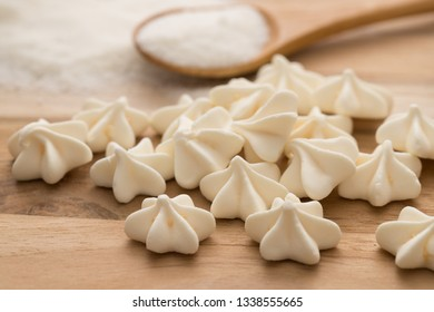 Sweet food. Meringue recipe. Delicious homemade meringues and ingredientes (egg and sugar) with cute spoon on wooden background