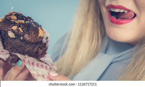 Sweet food sugar make us happy. Attractive blonde woman holds yummy chocolate cupcake in hand, open mouth, craving for cake. On blue