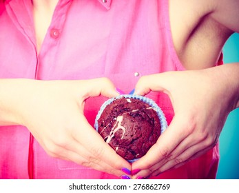 Sweet food sugar make us happy. woman holds chocolate muffin in hand making heart shape with fingers around cake closeup