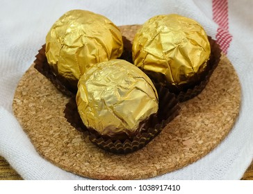 Sweet Food, Three Round Chocolate Candy Balls or Chocolate Bonbons in Golden Wrapper.