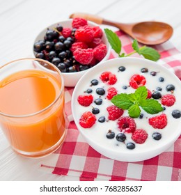 sweet food yoghurt with raspberry fruit and fresh mint , glass of juice, on white wooden background